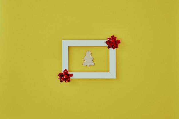 Cornice bianca con decorazioni natalizie e un albero di natale all'interno su sfondo giallo