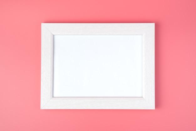 Cornice bianca con spazio per copiare, su sfondo rosa.