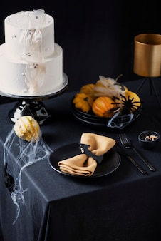 Torta glassata bianca con decorazione di halloween sul tavolo nero, messa a fuoco selettiva immagine
