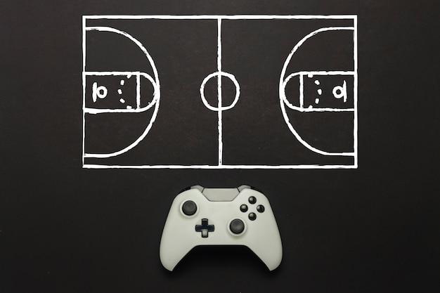 Gamepad bianco su sfondo nero. aggiunto uno schema di campi da basket. tattica del gioco. gioco di concetto di basket sulla console, giochi per computer. vista piana, vista dall'alto.