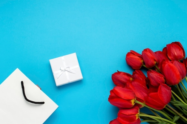 Sacchetto regalo bianco, un piccolo contenitore di regalo bianco e un mazzo di tulipani rossi su un blu. concetto offre un fidanzamento o un matrimonio, lo shopping