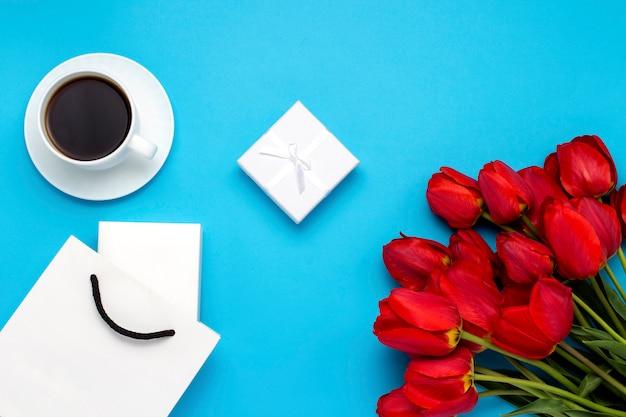 Sacchetto regalo bianco, una piccola confezione regalo bianca, una tazza bianca con caffè nero e un mazzo di tulipani rossi su sfondo blu. concetto offre un fidanzamento o un matrimonio, lo shopping