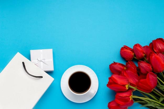 Sacchetto regalo bianco, una piccola confezione regalo bianca, una tazza bianca con caffè nero e un mazzo di tulipani rossi su un blu. concetto offre un fidanzamento o un matrimonio, lo shopping