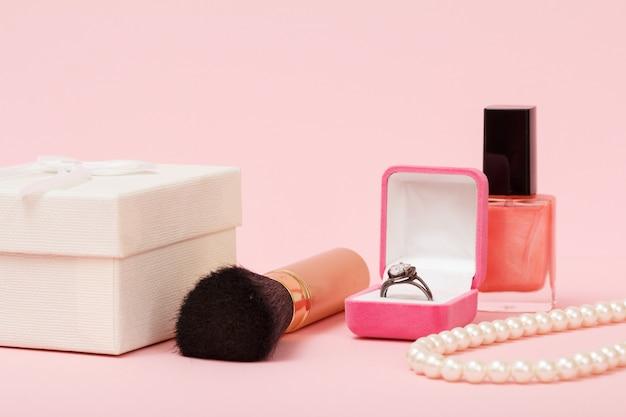 Confezione regalo bianca, pennello, anello in scatola, smalto per unghie e perline su sfondo rosa. gioielli, cosmetici e accessori da donna.