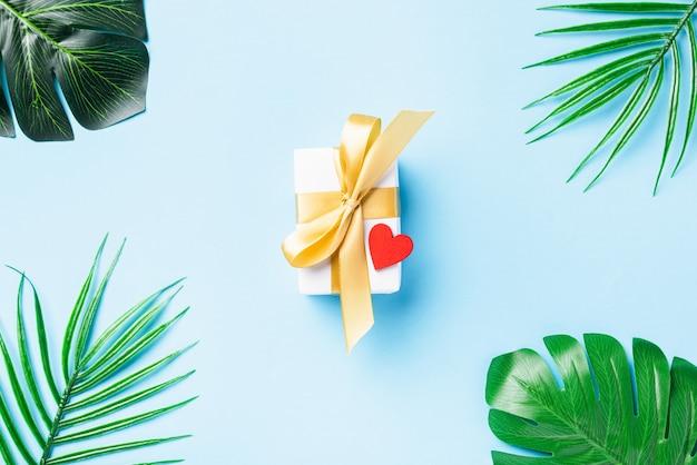 Cartolina con scatola regalo bianca con fiocco dorato e foglie verdi monstera della giungla tropicale e cuore rosso