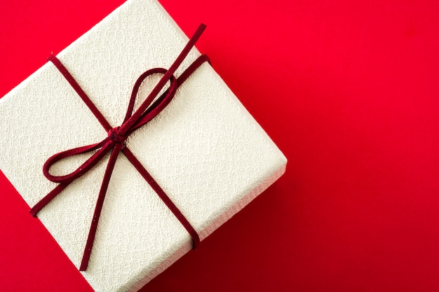 Confezione regalo bianca su sfondo rosso con spazio di copia