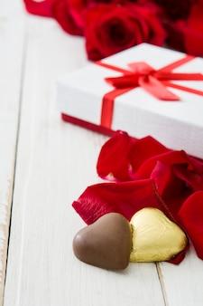 Contenitore di regalo, rose e cioccolato bianchi con forma del cuore sul copyspace di legno della tavola
