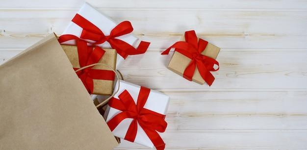 Confezione regalo bianca legata con un fiocco di nastro rosso in un sacchetto di carta su uno sfondo di legno bianco