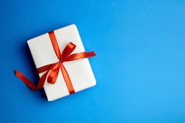 Confezione regalo bianca legata con nastro rosso sull'azzurro