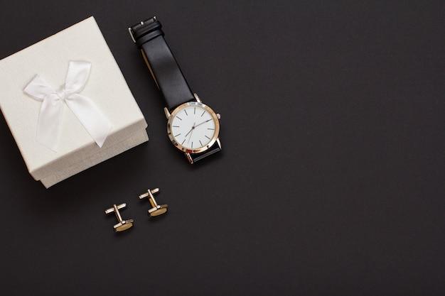 Confezione regalo bianca, orologio con cinturino in pelle nera e gemelli su sfondo nero. accessori per uomo. vista dall'alto con copia spazio.
