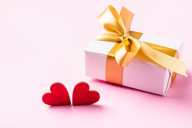 Confezione regalo bianca con nastro fiocco dorato e biglietto di auguri composizione cuori rossi legno