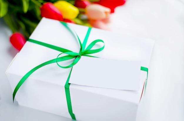 Scatola regalo bianca con nastro verde e bouquet di tulipani gialli