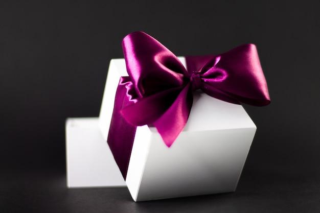 Confezione regalo bianca con nastro lilla su sfondo nero e scuro