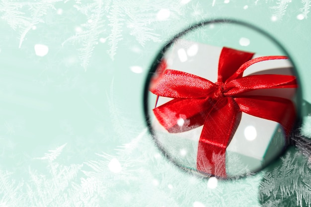 Una confezione regalo bianca con un fiocco rosso ingigantito da una lente d'ingrandimento tenuta a mano. su sfondo di menta