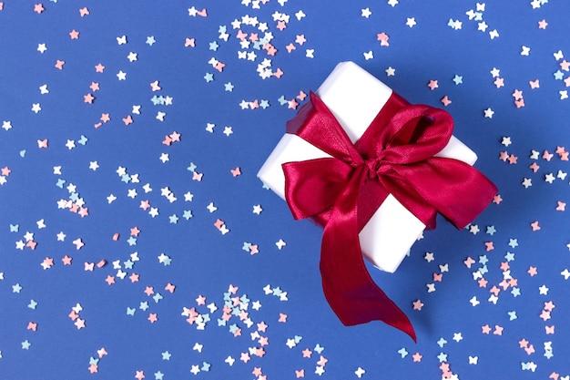 Confezione regalo bianca con nastro rosso su sfondo blu con stelle