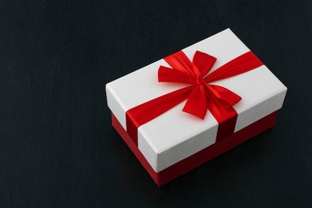 Confezione regalo bianca con nastro rosso e fiocco su sfondo nero.
