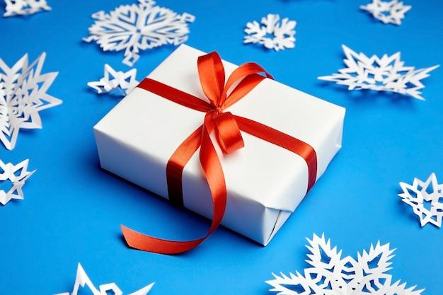 Scatola regalo bianca con nastro rosso e fiocchi di neve di carta sull'azzurro