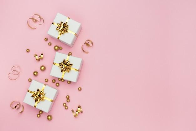 Scatole regalo bianche, decorazioni dorate e ornamenti su sfondo rosa pastello.