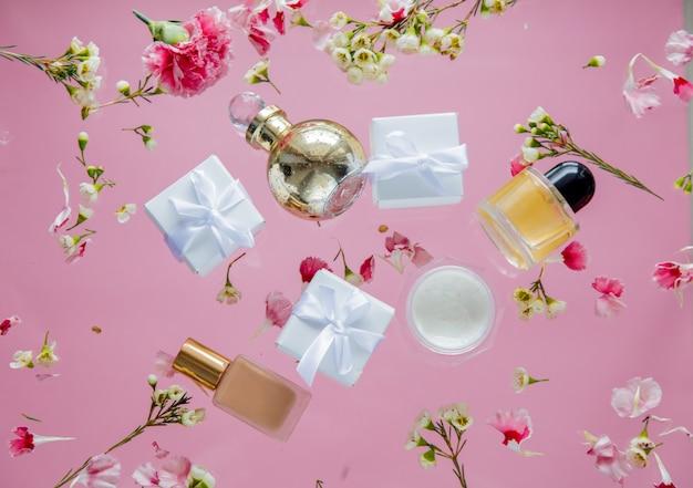 Scatole regalo bianche con cosmetici e fiori di chamelaucium sulla parete rosa