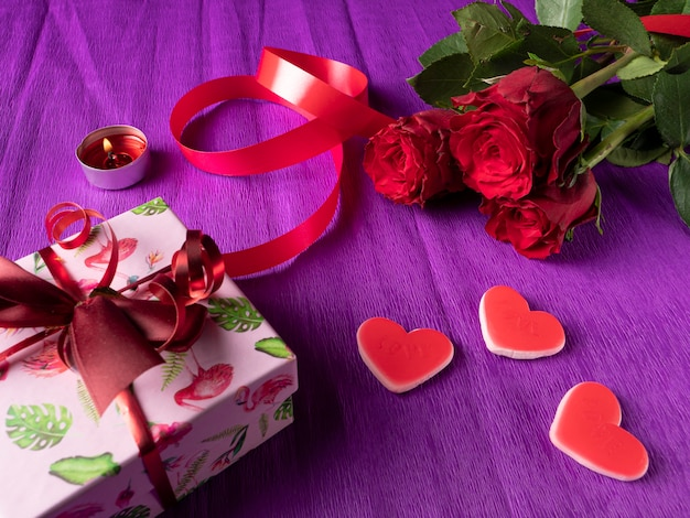 Regalo bianco accanto a cuori e nastro e rose rosse su viola
