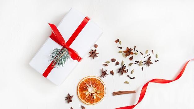 Un regalo bianco legato con un nastro rosso si trova su uno sfondo bianco circondato da un nastro rosso, fette d'arancia essiccate, bastoncini di cannella, anice stellato e chiodi di garofano secchi. focalizzazione morbida. vista dall'alto. lay piatto. natale