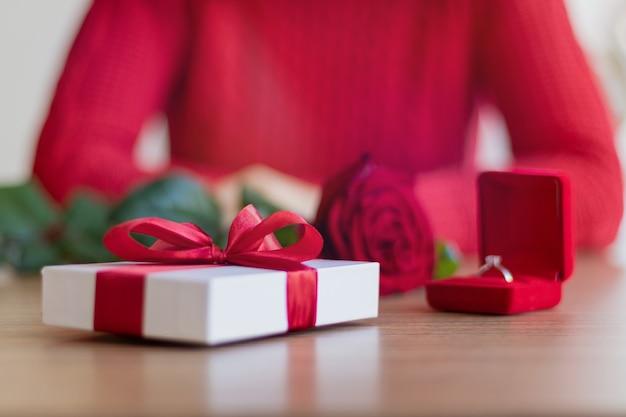 Giftbox bianco, due bicchieri da vino e un anello nella scatola che poggia sul tavolo. giovane donna che indossa un maglione rosso sorridente. presente con un nastro rosso. concetto di regali di san valentino e vacanze invernali.