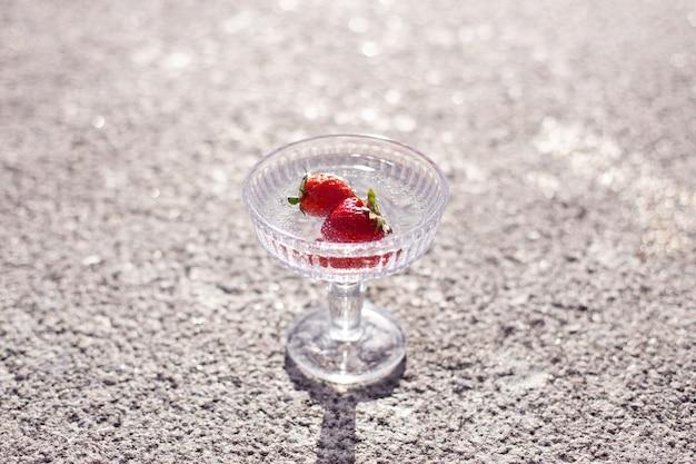 Bicchiere d'acqua bianco con fragola su sfondo grigio cemento