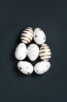 Forma di uovo di pasqua bianco e oro su sfondo nero