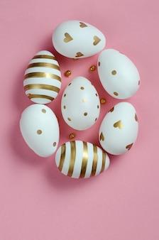 Forma di uovo di pasqua bianco e oro su sfondo rosa
