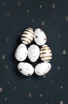 Uova di pasqua bianche e oro su sfondo nero fantasia