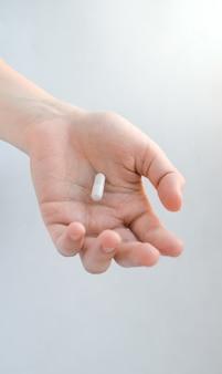 Una pillola bianco-grigia a forma di capsula giace in una mano femminile tesa