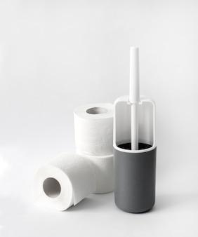 Scopino e carta igienica in plastica bianca e grigia su sfondo bianco. copia spazio