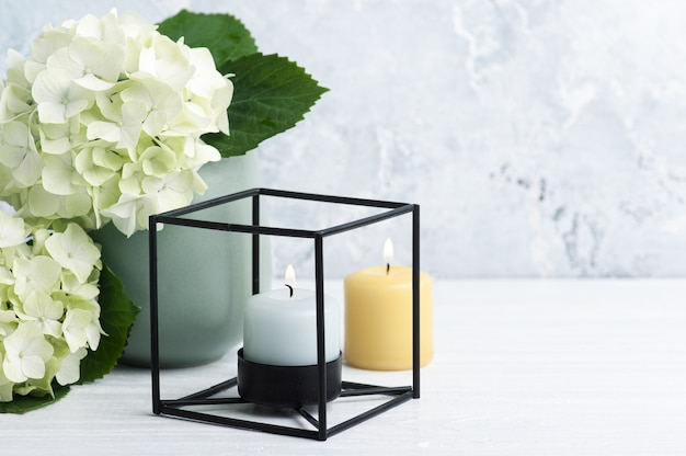 Hortensia verde bianco fiorisce in vaso e candele accese