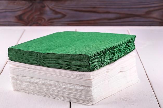Tovaglioli bianchi e verdi per il tavolo da pranzo su un tavolo luminoso