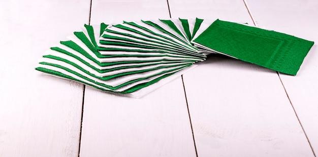 Tovaglioli bianchi e verdi per il tavolo da pranzo su un tavolo in legno chiaro
