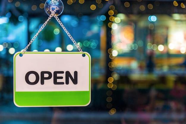 Un segno aperto bianco e verde che appende sulla porta di vetro della caffetteria durante la notte
