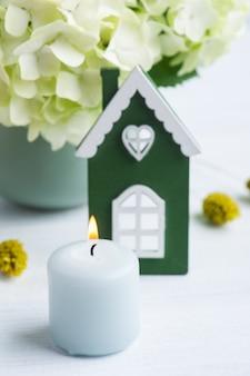 Casa in legno verde bianca, fiori di ortensie in vaso e candele accese