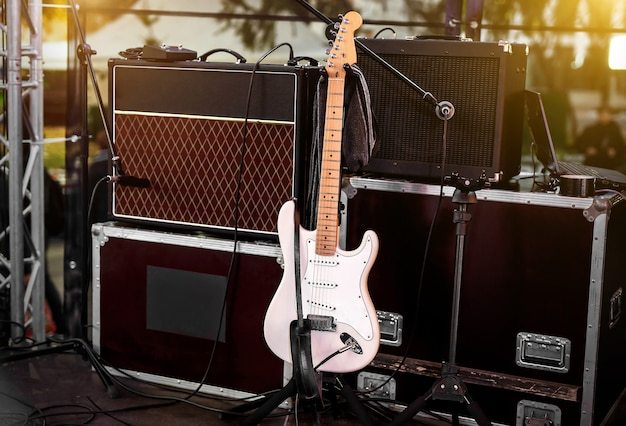 Chitarra bianca sul palco tra amplificatori e altre apparecchiature musicali.