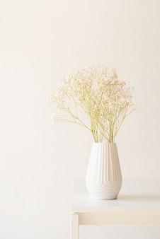 La gypsophila bianca fiorisce in vaso bianco sul tavolo da cucina e sul fondo bianco della parete