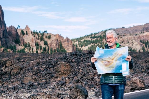 Capelli bianchi vecchio adulto che guarda e controlla una mappa cartacea sulla strada di un'attività alternativa per il tempo libero o una vacanza in montagna - persone che si godono l'ambiente all'aperto