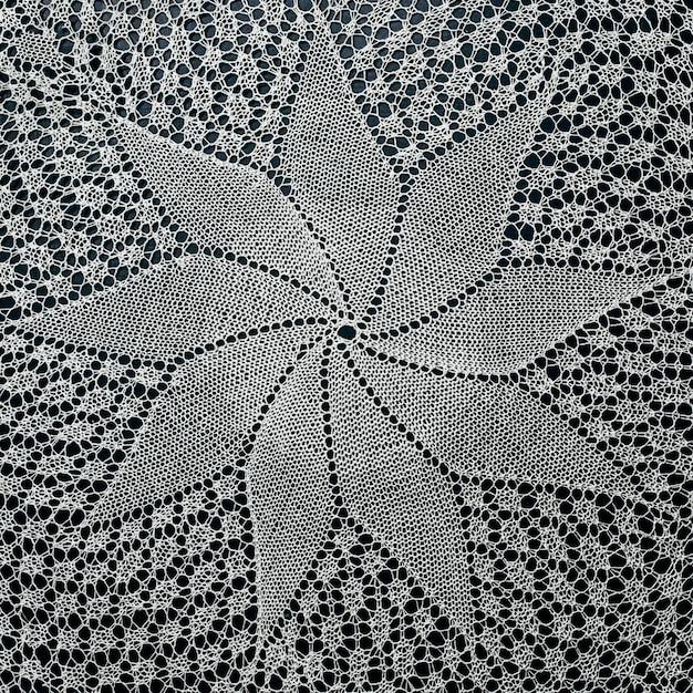 Pizzo lavorato a mano bianco su superficie nera.