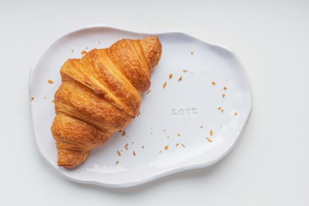 Piatto di argilla bianca fatta a mano con croissant freschi su un tavolo bianco