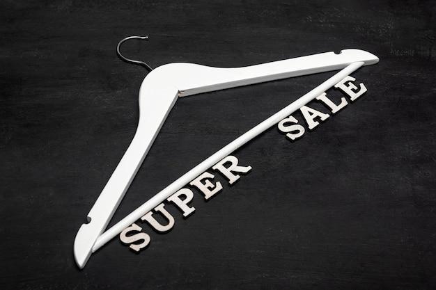 Appendiabiti bianco e testo super vendita su sfondo nero. sconti. vendita stagionale.