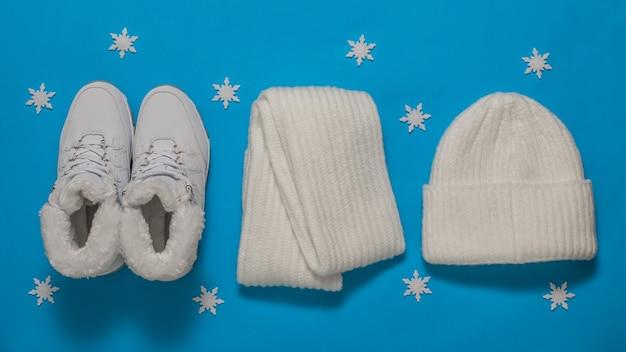 Cappello bianco, sciarpa e sneakers in pelliccia con fiocchi di neve. accessori invernali alla moda.