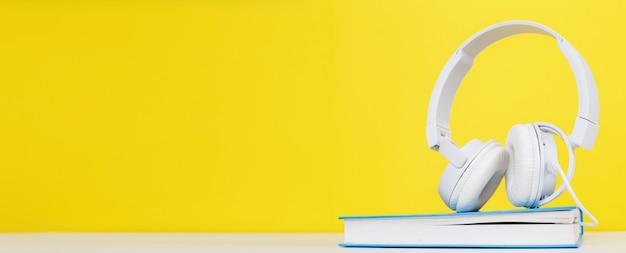 Cuffie bianche e libro su sfondo giallo