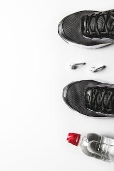 Cuffie bianche, una bottiglia di acqua fresca e scarpe da ginnastica sulla superficie bianca. natura morta e concetto di assistenza sanitaria. lay piatto, vista dall'alto. copi lo spazio per testo.