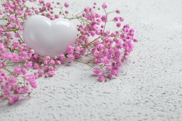 Un cuore bianco su uno sfondo di fiori rosa ha un posto per il testo.