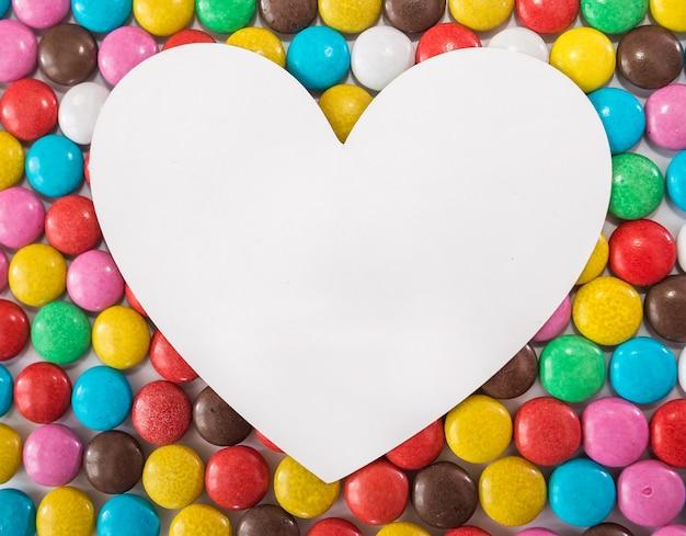 Cuore bianco su uno sfondo di dolci colorati rotondi. copia spazio.