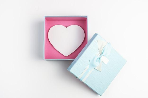 Cuore bianco in una scatola blu con un coperchio aperto su uno sfondo bianco.