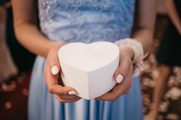 Scatola bianca a forma di cuore con diamante nelle mani della ragazza in blu dresd